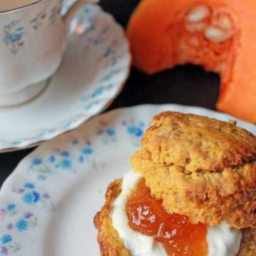 A pumpkin scone with cream and jam on a vintage plate next to a cup of tea.