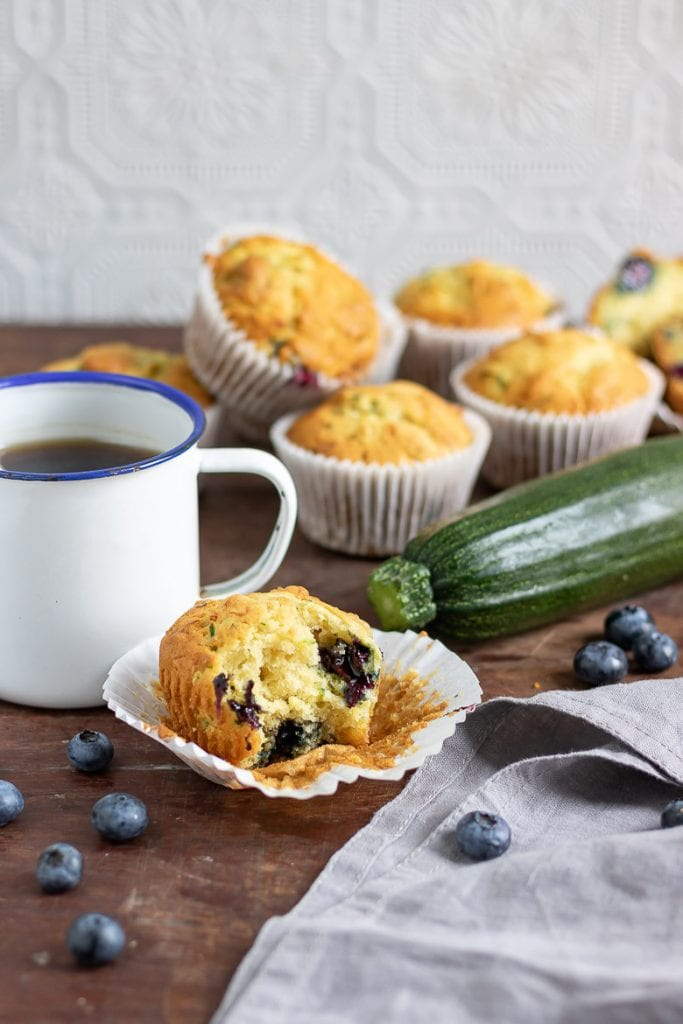 A blueberry courgette muffin with a bite taken out in front of mug of coffee and pile of zucchini muffins
