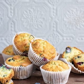 A pile of blueberry courgette muffins on wooden table