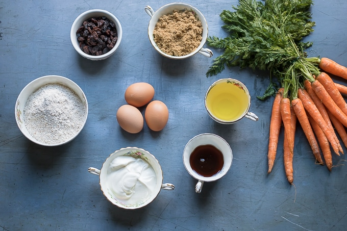Ingredients for easy carrot cake: carrots, whole wheat flour, raisins, brown sugar, eggs, oil, maple syrup, yogurt