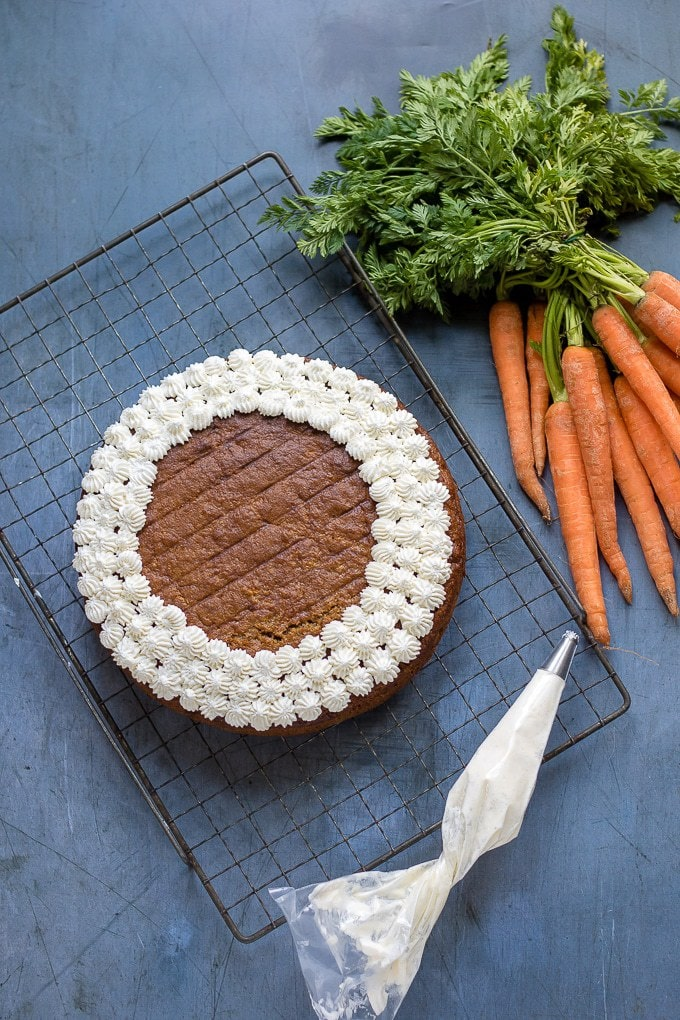 Overhead of easy carrot cake with maple whipped cream piped in dots around the edge. Next to a bunch of carrots.