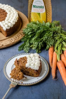 A slice of easy carrot cake (nut-free) with a bunch of carrots