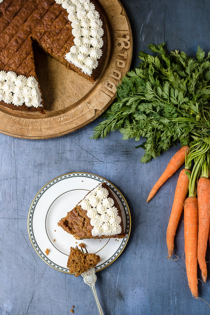 A slice of easy carrot cake next to the cake and a bunch of carrots. Decorated with dots of maple whipped cream. A great carrot cake recipe.