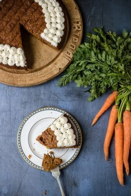 A slice of easy carrot cake next to the cake and a bunch of carrots. Decorated with dots of maple whipped cream.