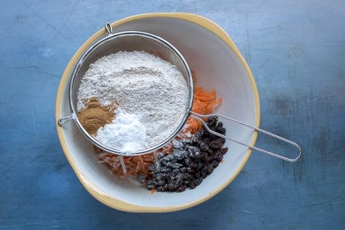 How to make easy carrot cake: Step 2 - Sift in the whole wheat flour, baking soda, baking powder, cinnamon and salt