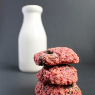 A stack of cookies in front of a milk bottle.