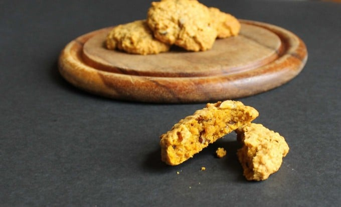 Pumpkin Hazelnut Oat Biscuits on a wooden tray with a broken cookie at the front.