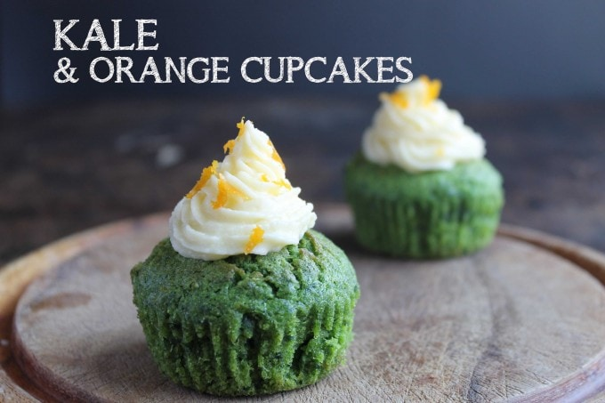 Kale and Orange Cupcakes with Orange Icing text overlay on an image of two bright green kale cupcakes.
