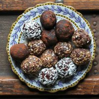 A plate of vegan chocolate beetroot bliss balls on a wooden vintage trunk. You only need 8 ingredients and 10 minutes to whiz up these beetroot protein balls. They're full of protein, tasty and so easy. Store in the fridge or freezer and grab a few for breakfast or a snack.