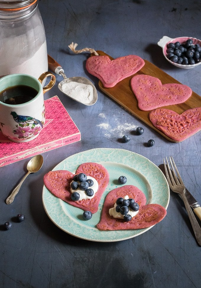 Heart-shaped beet pancakes with yogurt and blueberries on a plate surrounded my a mug, more heart pancakes and blueberries