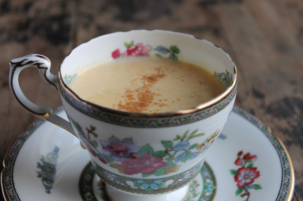 Sweet Potato Latte in a vintage teacup on a wooden table.
