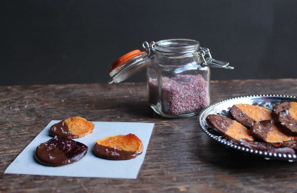 Slices of beets and sweet potatoes dipped in chocolate on a piece of paper.