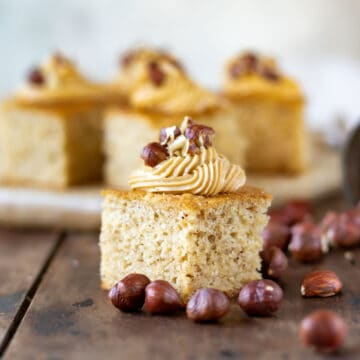 Slice of cake topped with frosting and hazelnuts.