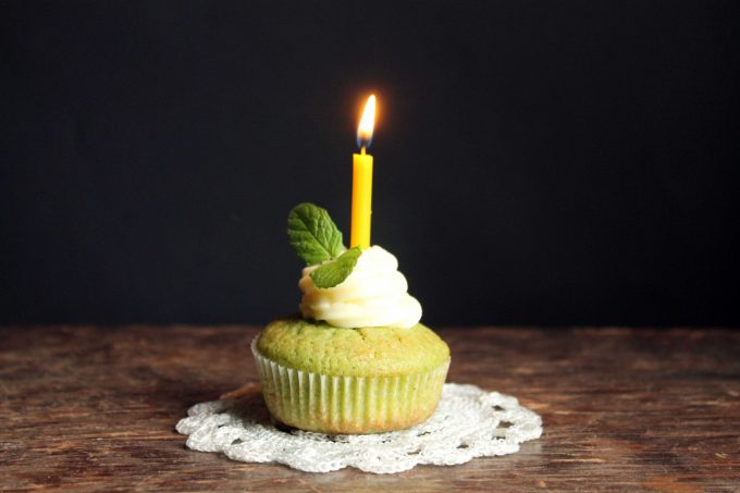 A cupcake with a lit candle.