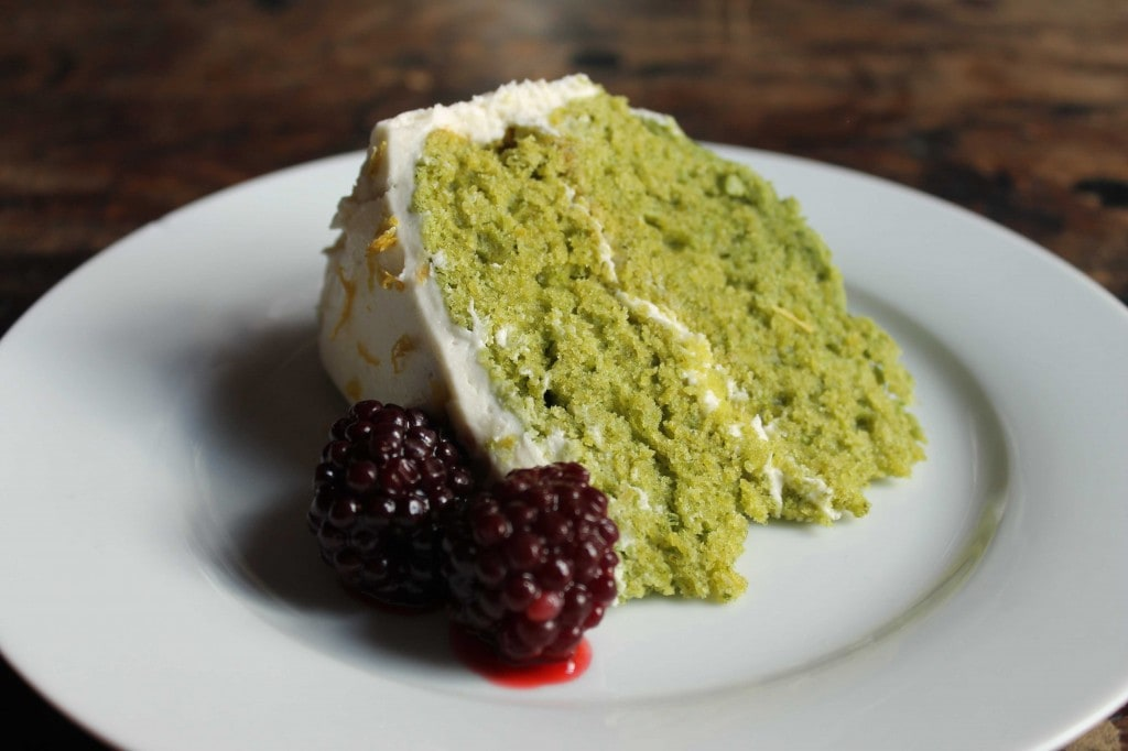 A slice of bright green Lemon Stinging Nettle Layer Cake with blackberries