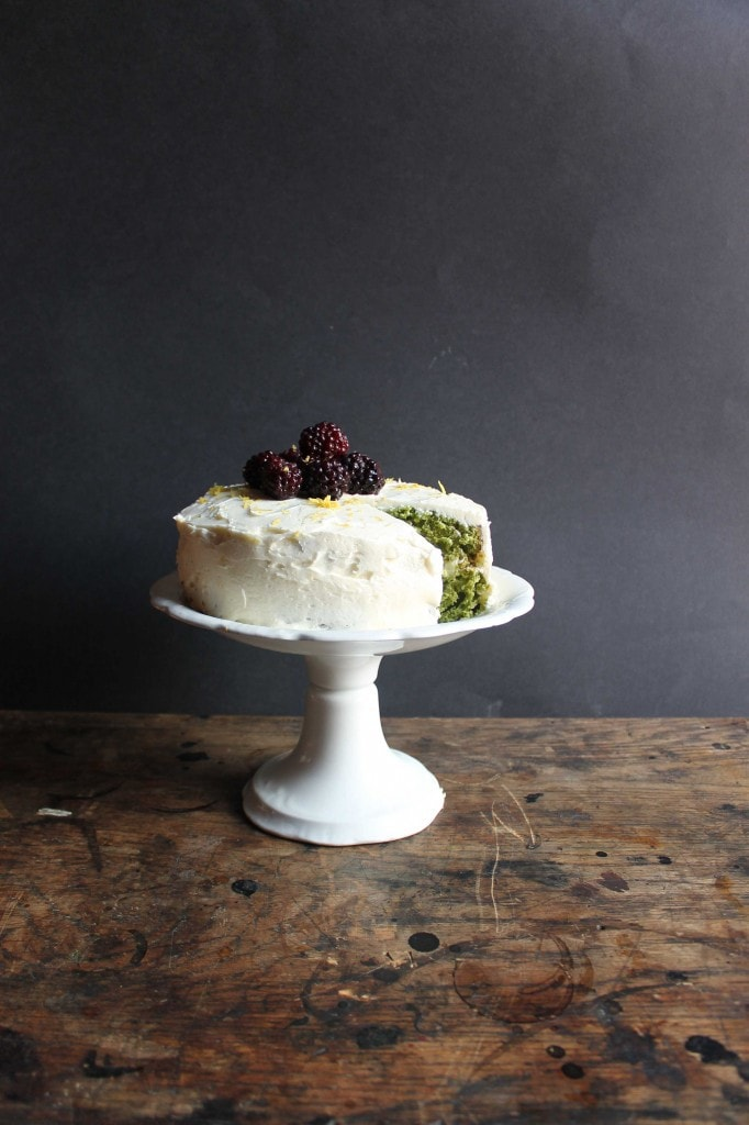 A cake stand with a Stinging Nettle Cake with a slice taken out showing the green cake inside