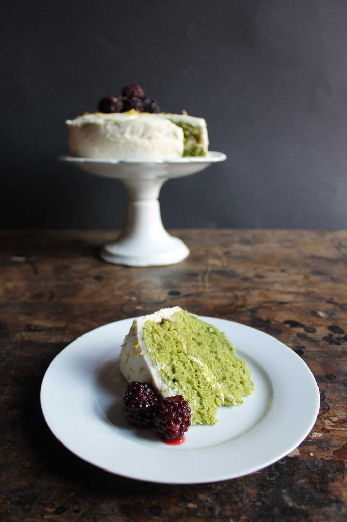 A slice of green Stinging Nettle Cake on a plate in front of the cake on a cake stand.