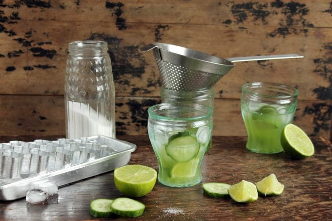 Cucumber Caipirinha Cocktail being made with ingredients around glass