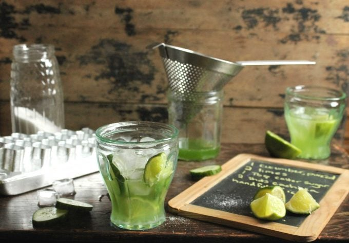 Cucumber Caipirinha Cocktail in a glass next to ice, a sieve and recipe on chalkboard