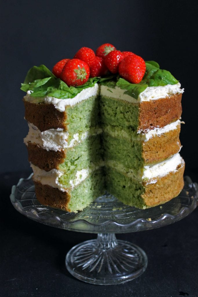 Spinach Coconut Yogurt Cake with a slice cut out showing the green cake. Topped with strawberries.