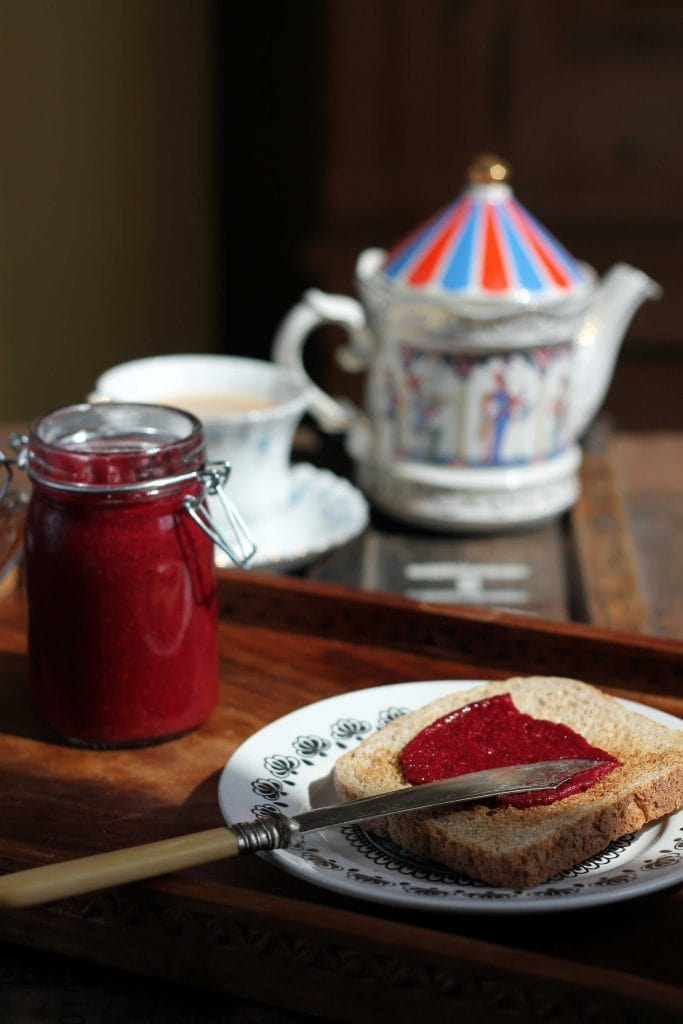 A jar of raspberry beet chia jam, plus some spread on toast, in front of a teapot and cup of tea.