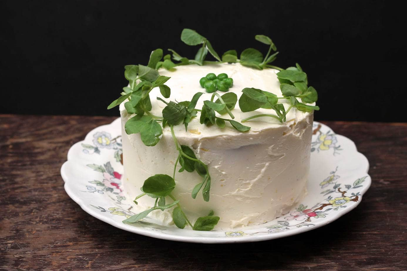 Cake on a vintage plate with pea shoots piled on top.