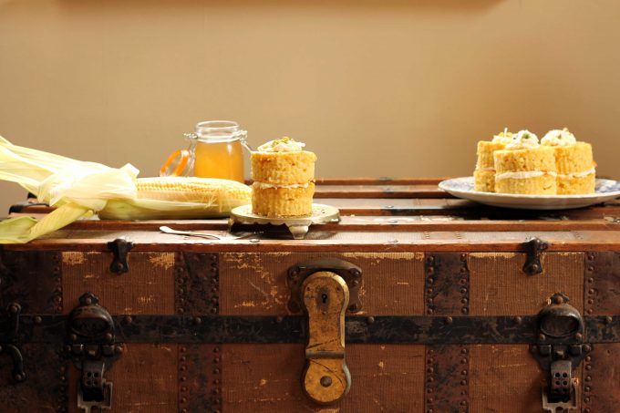 Mini Coconut Corn Cakes on a vintage trunk next to a jar of corn cob jelly