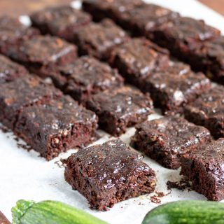 Close up of cut zucchini brownies with a zucchini in the front