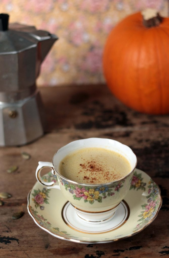 Pumpkin Spice Latte with Pumpkin Seed Milk in a vintage teacup in front of a coffee pot and a pumpkin.