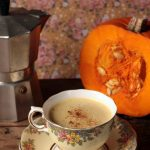 A table with a teacup, pumpkin and coffee pot.
