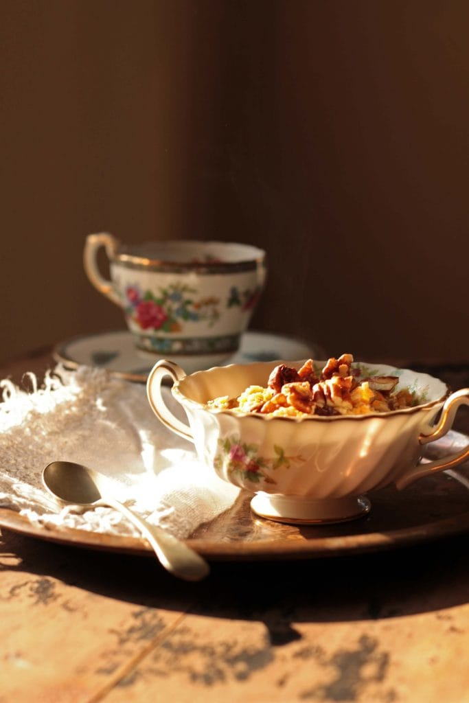 A tray on a table, with oatmeal in a bowl and a vintage cup of tea.