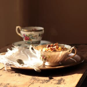 A vintage bowl of oatmeal next to a teacup.