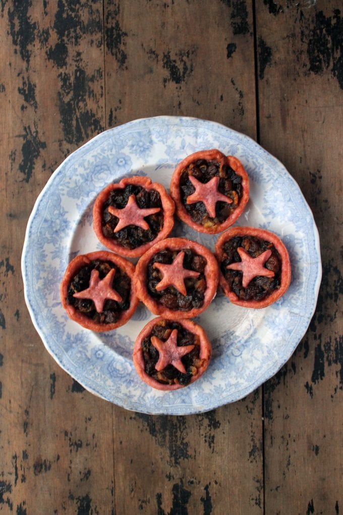 Christmas Mince Pies with Beet Pastry on a vintage plate on a wooden table. Bright purple pastry with stars.