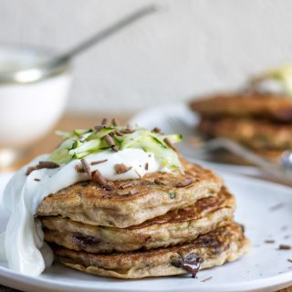 A stack of zucchini pancakes on a plate, topped with maple yogurt