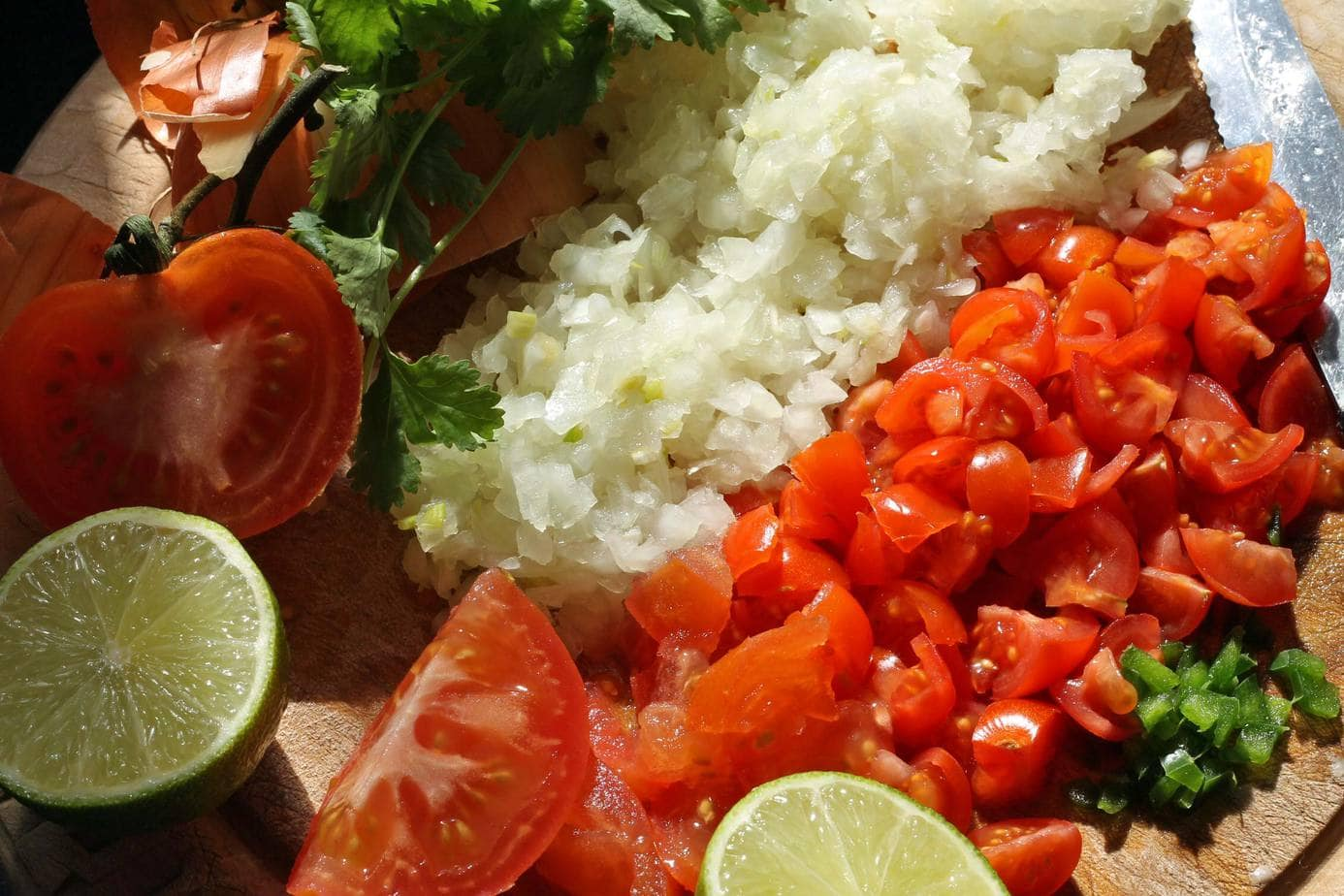 Pico de Gallo ingredients - chopped onion, tomato, cilantro, peppers, plus lime wedges.