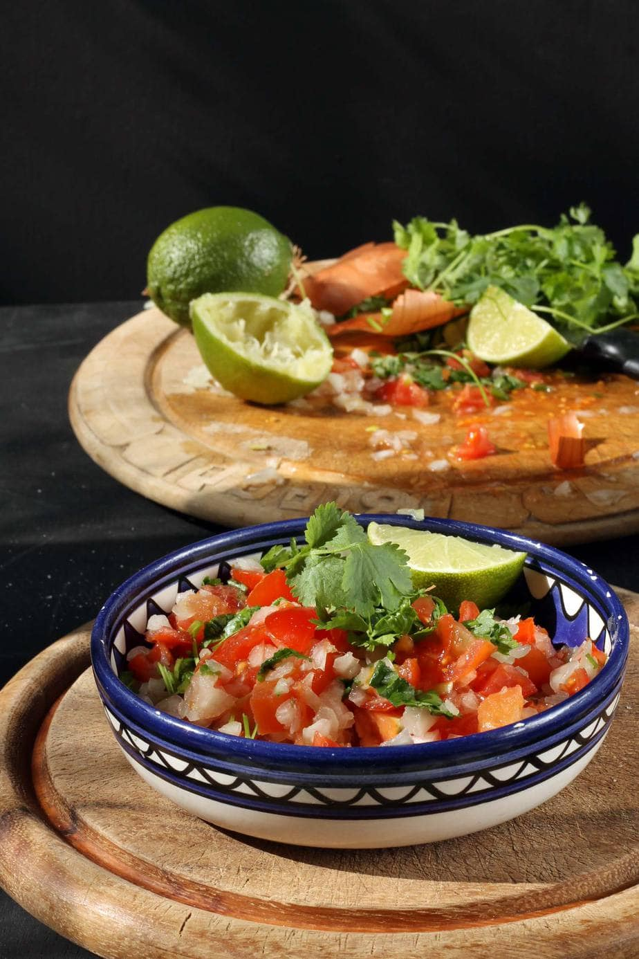A bowl of Pico de Gallo on a wooden board, with coriander/cilantro on top and a wedge of lime.