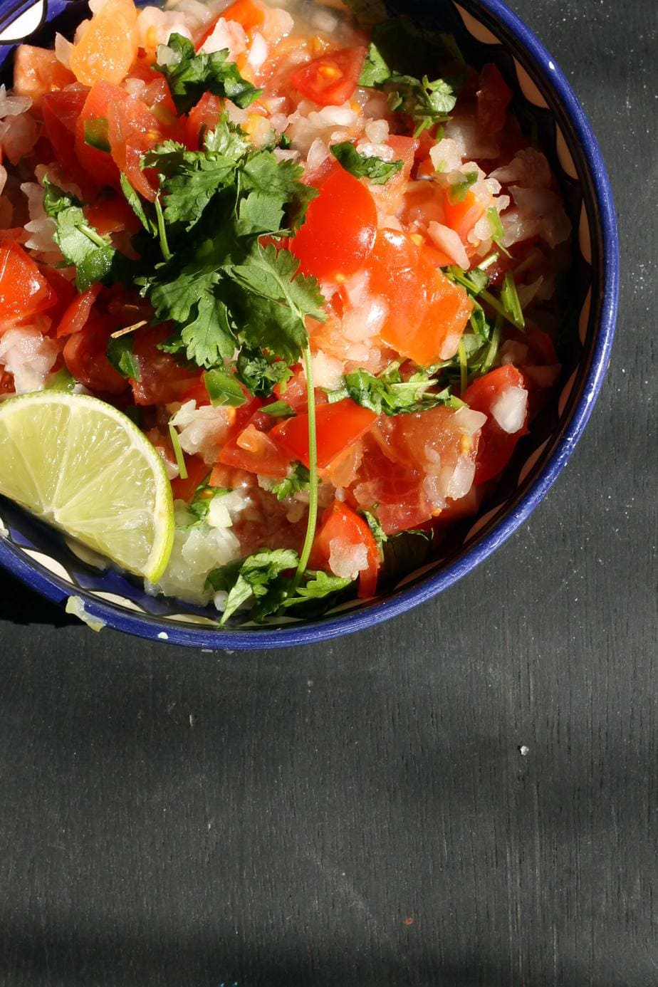 Pico de Gallo in a bowl with coriander/cilantro and a wedge of fresh lime.