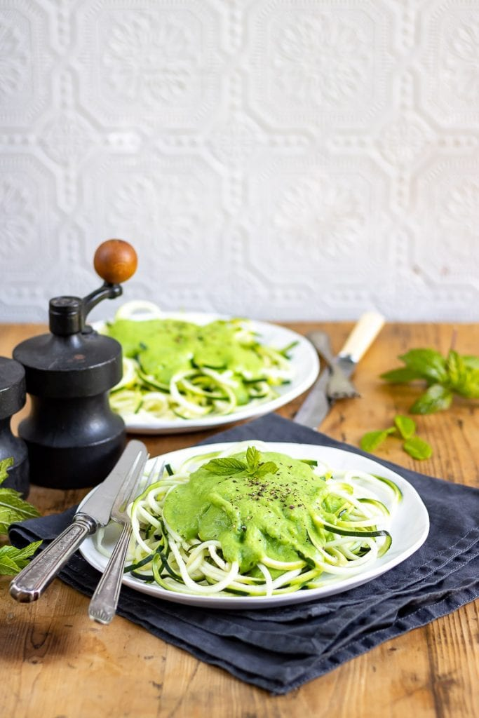 Courgetti with Pea and Mint Sauce. A plate with spiralized courgette (zucchini) zoodles, topped with pea sauce.