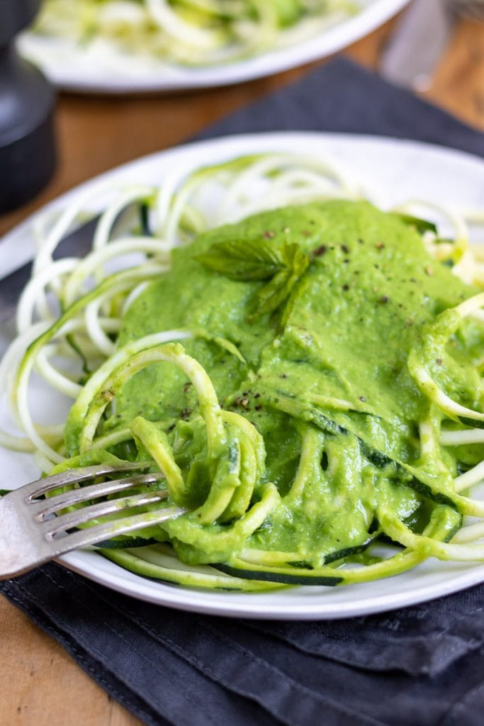 Close up of a fork taking courgetti recipe with pea sauce on top.