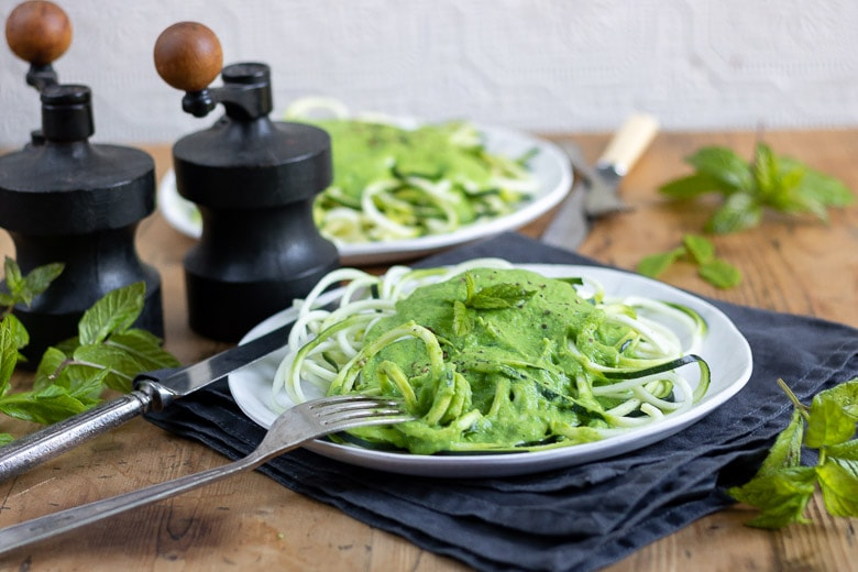 A plate on a napkin with zoodles (courgette or zucchini pasta) covered in a pea and mint sauce