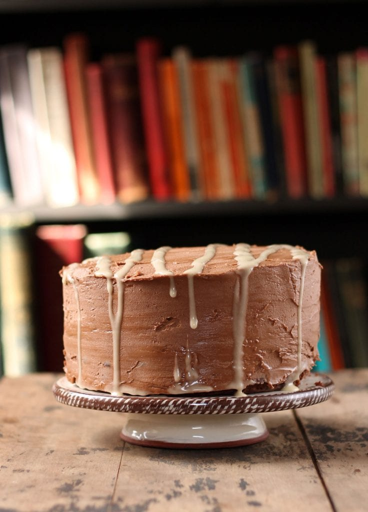 A cake on a cake stand in front of a bookshelf.
