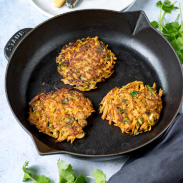 Moroccan Carrot Fritters in a skillet next to plates and cutlery