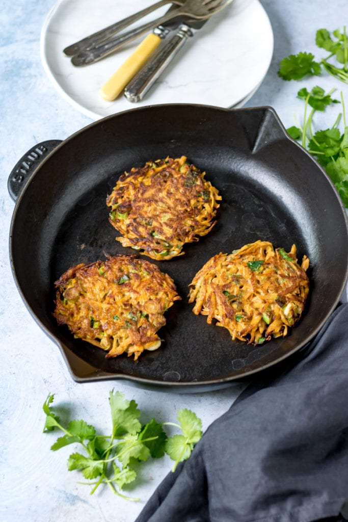 Moroccan Spiced Chickpea and Carrot Fritters recipe on a vintage plate topped with sour cream and spring onions