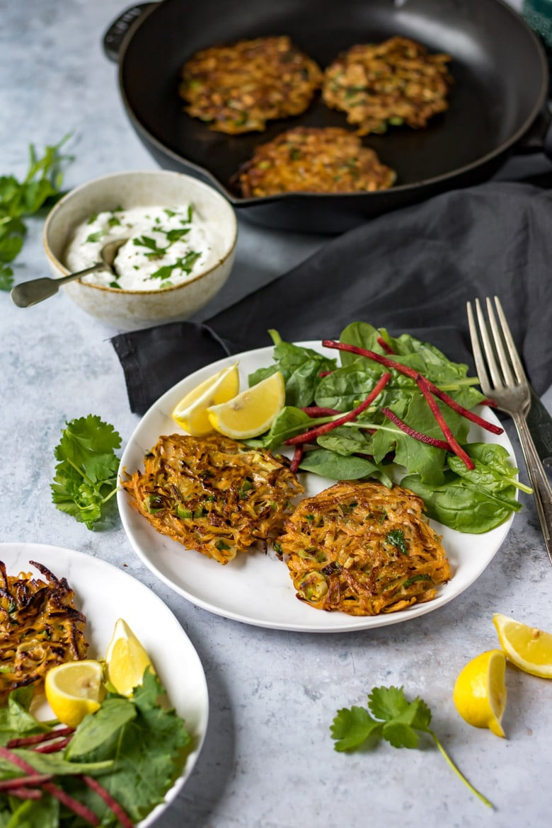 Two plates with Moroccan spiced carrot chickpea fritters, with salad and lemon wedges.