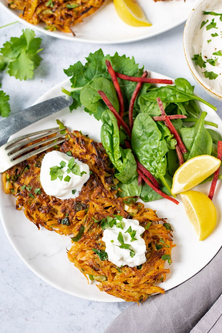 A plate with Moroccan Carrot Fritters, with sour cream, salad and wedges of lemon