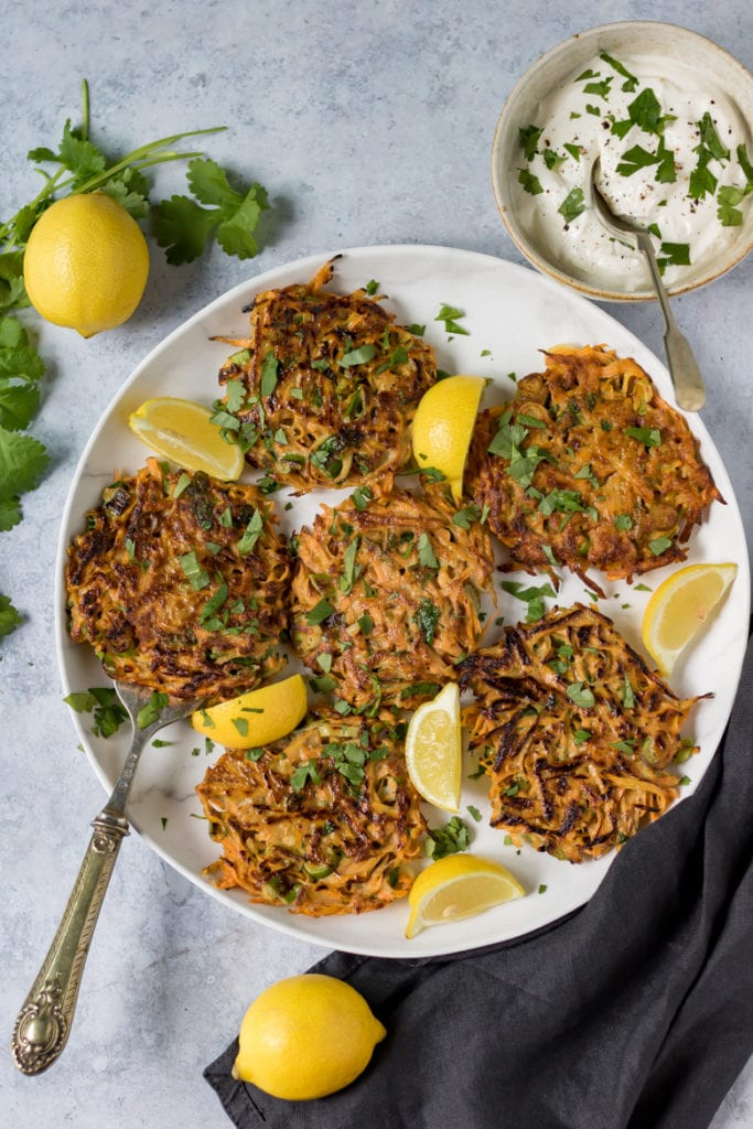 A plate of Moroccan spiced chickpea and carrot fritters, with wedges of lemon