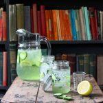 A table with drinks and a jug, in front of bookshelves.