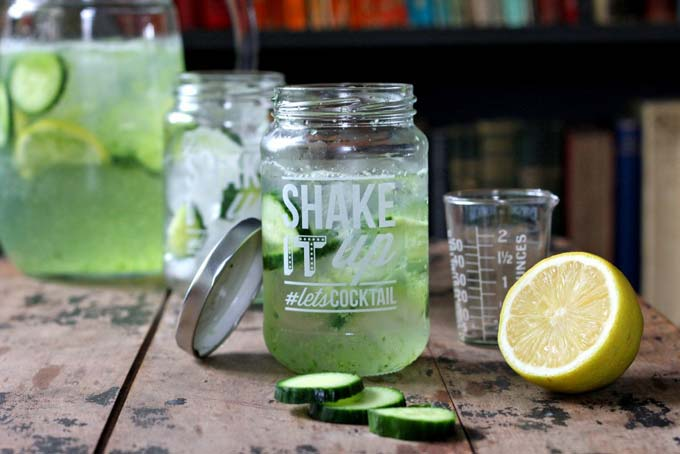 A jar glass full of fresh cucumber gin and tonic, next to slices of lime and cucumber