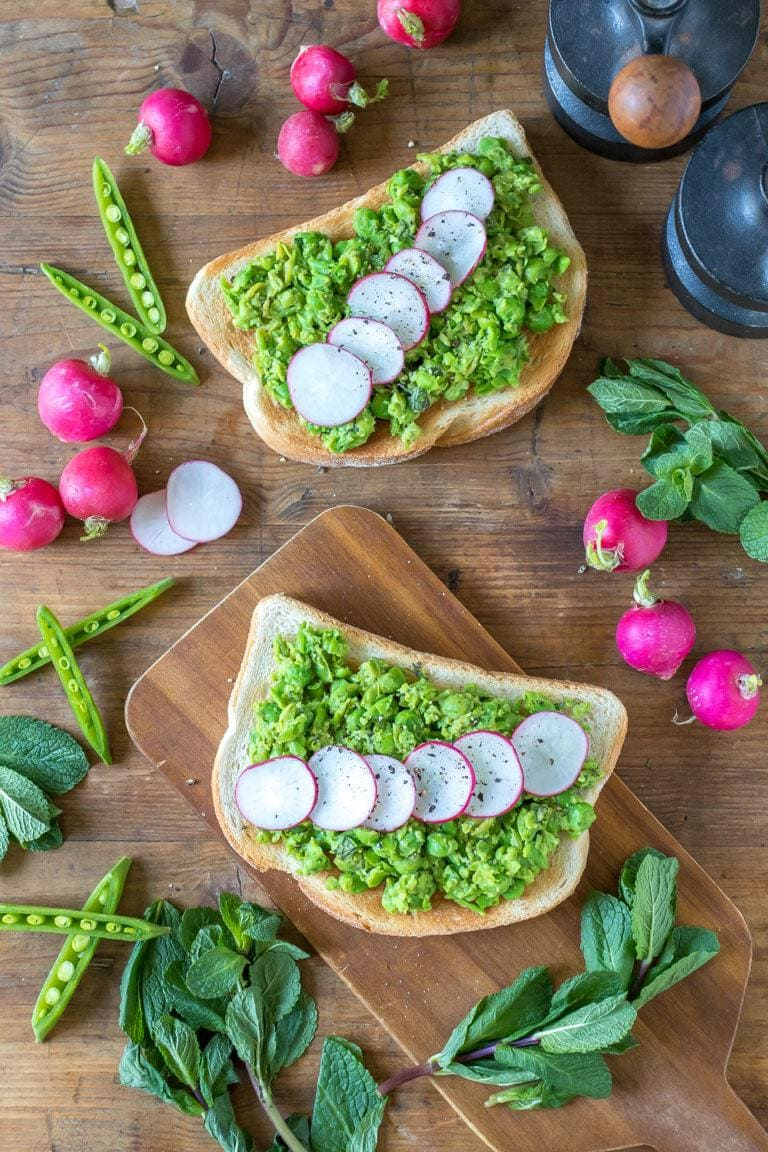 Overhead shot of crushed peas on toast with mint and radishes. Radishes, peas and fresh mint are strewn around the table. Get the easy 5 minute vegetarian or vegan brunch recipe now.