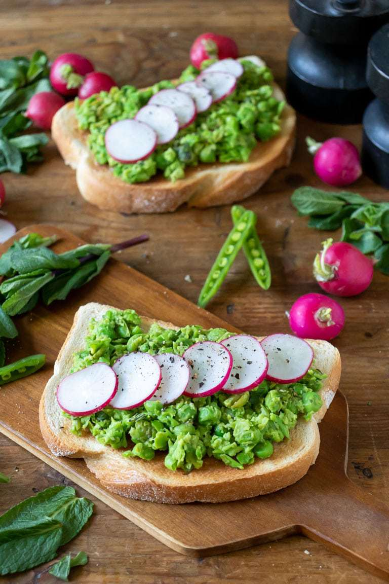 Close up of peas on toast with mint and radishes with peas and radishes on the table. Peas on toast with mint and radishes is a vibrant and fresh, Spring-like vegan brunch, breakfast or lunch. You only need 5 ingredients and 5 minutes for this tasty recipe.